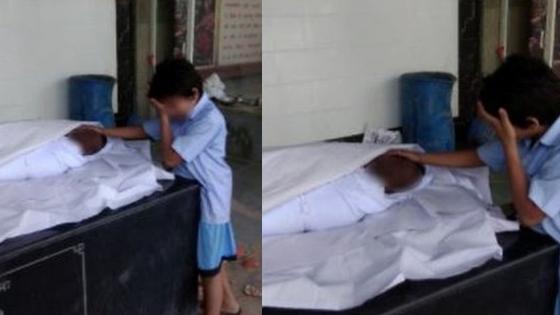 Imagem de menino ao lado de pai morto
